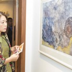 A visitor taking keen interest in the art exhibit by Pakistan women artist.