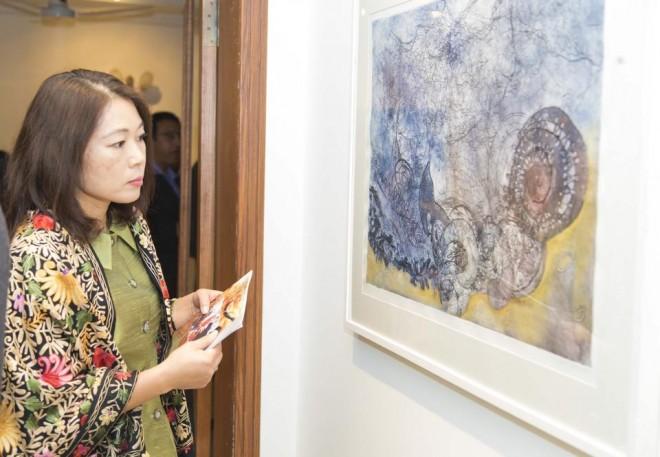 A visitor taking keen interest in the art exhibit by Pakistan women artists.