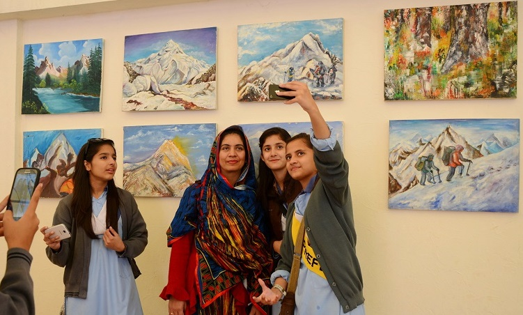 Student taking selfies with their artworks on Climate Change at at 5th Pakistan Mountain Festival in Islamabad