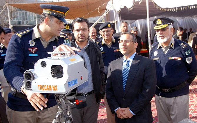 Speed checking cameras being inspected by the officials and police officers.