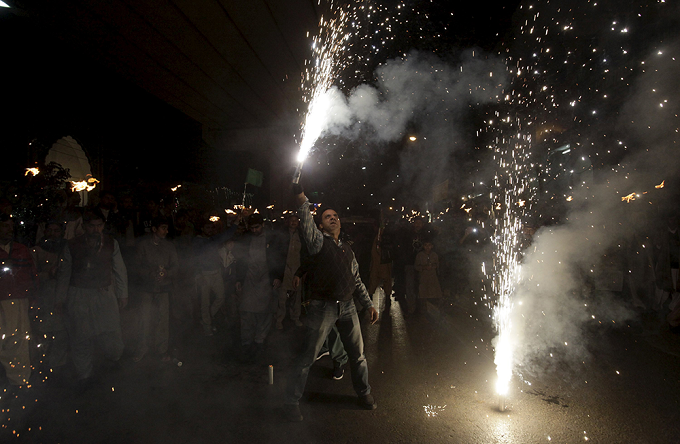A man lights fireworks during a procession ahead of Eid-e-Milad-ul-Nabi celebration in Lahore.