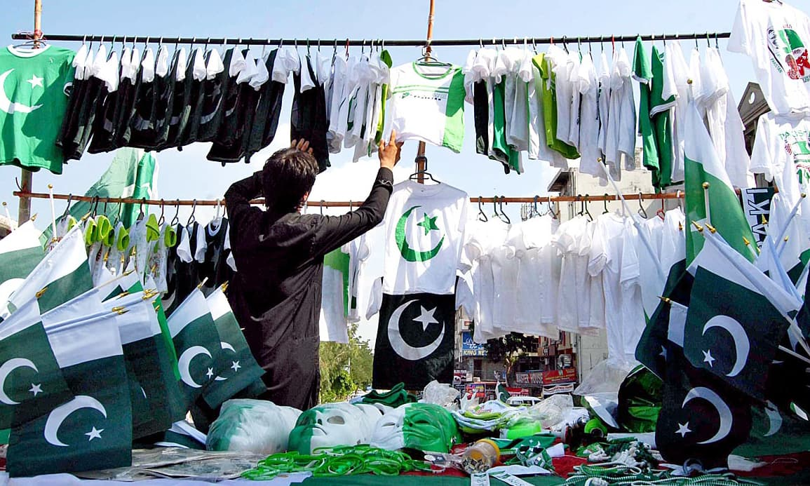 A vendor sells national flags of all shapes and sizes in Islamabad. Photo: APP/Saeed-ul-Mulk