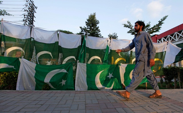 A man walks past a Pakistani flag display along a roadside as people prepare to celebrate Independence Day in Rawalpindi. Photo: Reuters