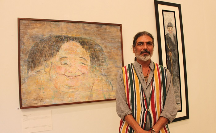 Pakistani artist Farrukh Shahan with his paintings at joint exhibition by Pakistani and Chinese artists at PNCA in Islamabad on 18 Oct. 2016. Photo: Sana Jamal