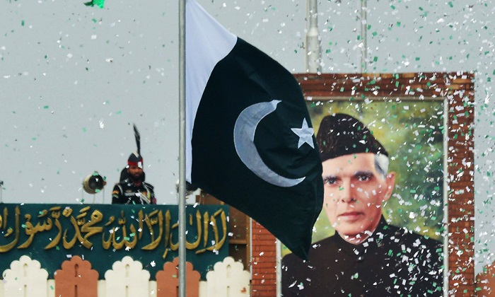 The portrait of Muhammad Ali Jinnah is seen at the Wagah border post as a Pakistani Ranger (top) unfurls the Pakistani national flag during a ceremony to celebrate Independence Day. —AFP